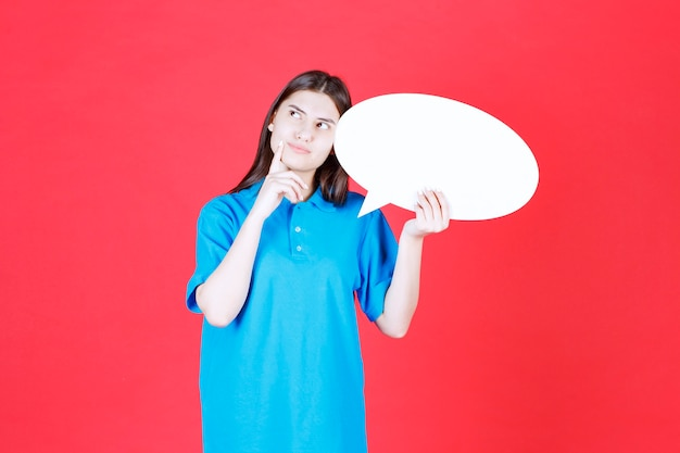 Fille en chemise bleue tenant un panneau d'information ovale et a l'air confuse et réfléchie
