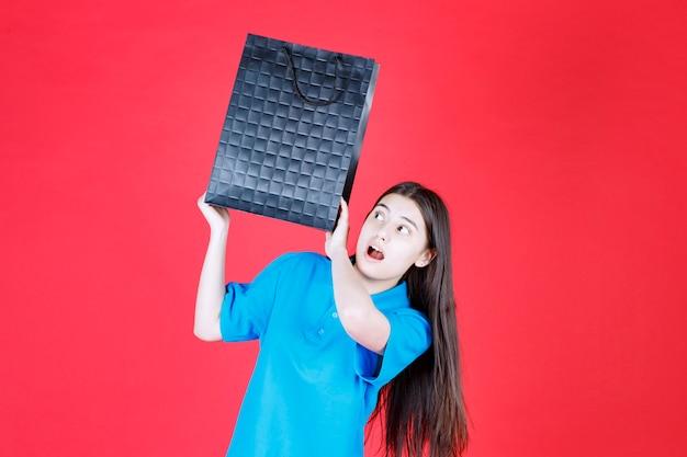 Fille en chemise bleue tenant un sac à provisions violet et a l'air ravie et stressée.