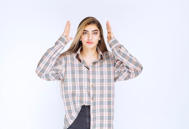 Fille en chemise à carreaux montrant la largeur d'un objet