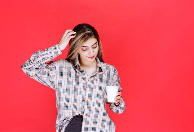 Fille En Chemise à Carreaux Tenant Une Tasse De Café Jetable Blanche Et A L'air Réfléchie Ou A De Bonnes Idées Photo gratuit