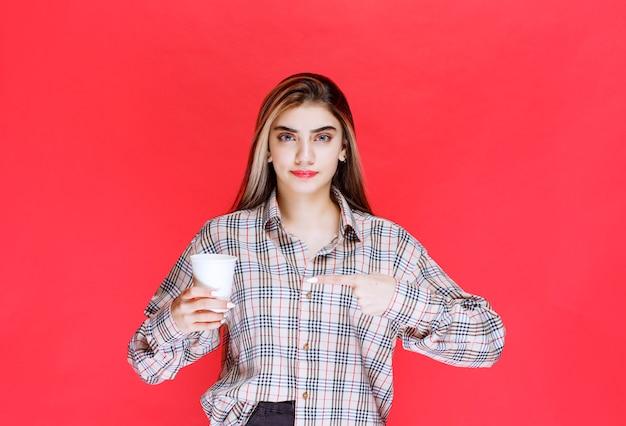 Fille en chemise à carreaux tenant une tasse de café jetable blanche