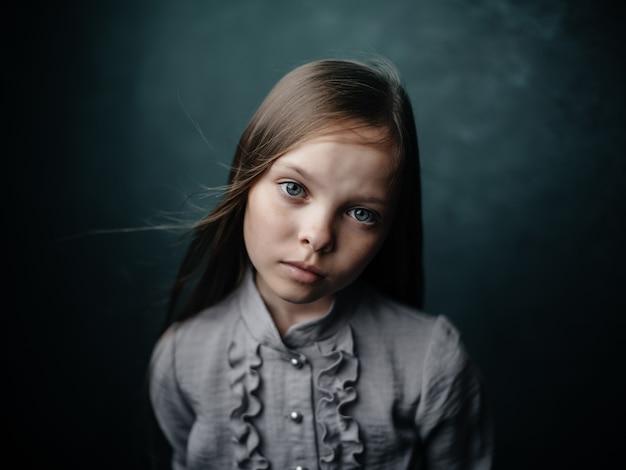 Fille en chemise grise posant des émotions de studio gros plan. photo de haute qualité