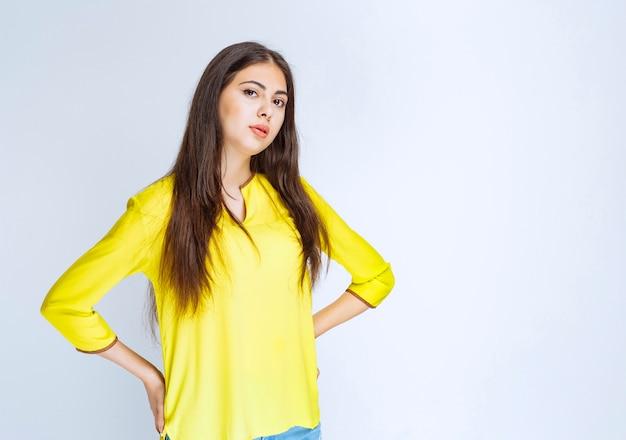 Fille en chemise jaune donnant des poses neutres.