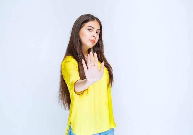 Fille en chemise jaune saluant ou arrêtant quelqu'un.
