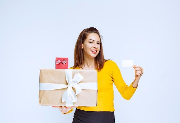 Fille en chemise jaune tenant des coffrets cadeaux et présentant sa carte de visite.