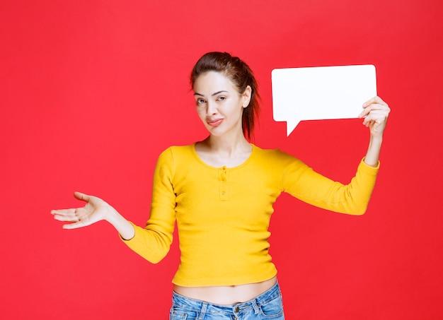 Fille en chemise jaune tenant un panneau d'information rectangle et semble confuse et incertaine.