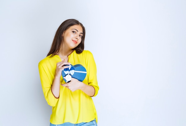 Fille en chemise jaune tenant et promouvant une boîte cadeau en forme de coeur bleu.