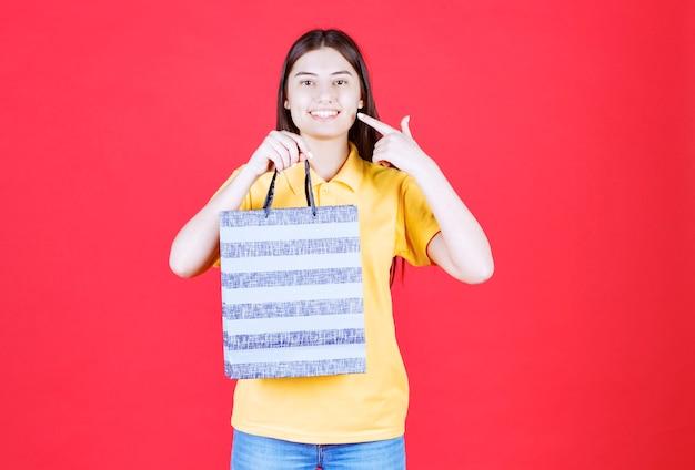 Fille en chemise jaune tenant un sac bleu avec des motifs dessus
