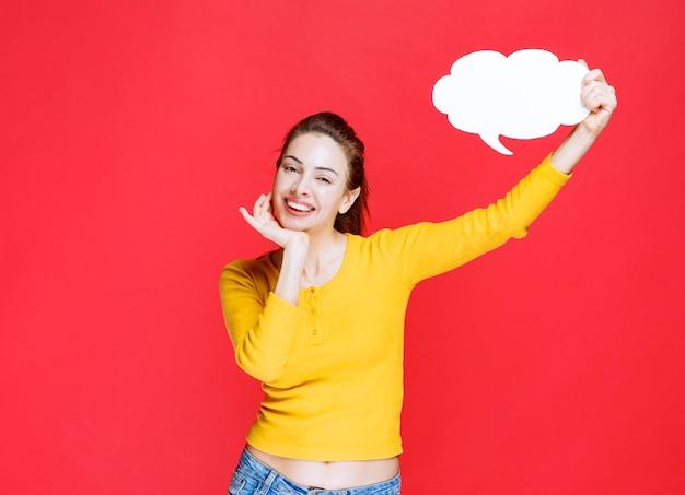 Fille en chemise jaune tenant un tableau d'informations en forme de nuage.