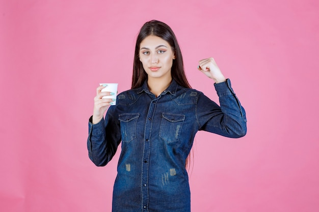 Fille en chemise en jean ayant une tasse de café et se sentant puissant