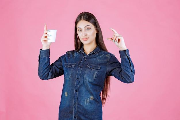 Fille en chemise en jean montrant la quantité de café dans la tasse