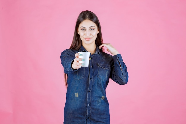 Fille en chemise en jean offrant une tasse de café à son amie