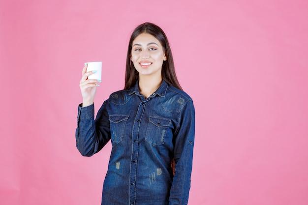 Fille en chemise en jean tenant une tasse de café et se sent positif