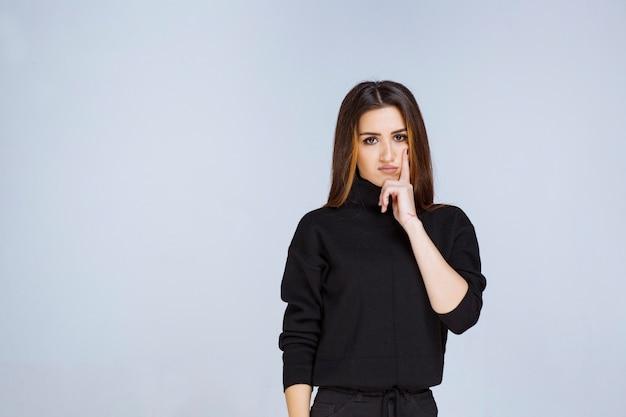 La fille en chemise noire a l'air réfléchie. photo de haute qualité