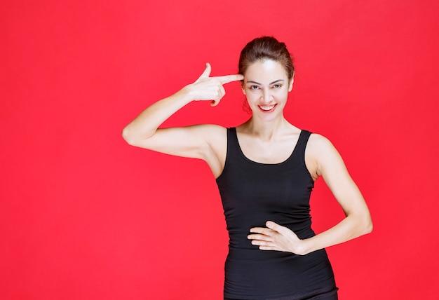 Fille en chemise noire pointant sur elle-même. photo de haute qualité