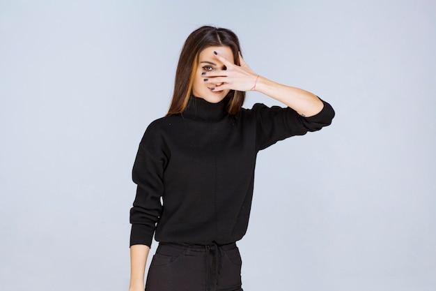 Fille en chemise noire regardant à travers ses doigts. photo de haute qualité