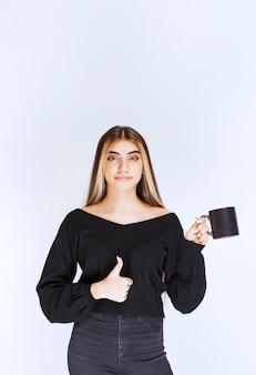 Fille en chemise noire tenant une tasse de café noire et appréciant le goût. photo de haute qualité