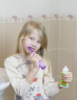 Fille en chemise de nuit avec une brosse à dents électrique dans la salle de bain.