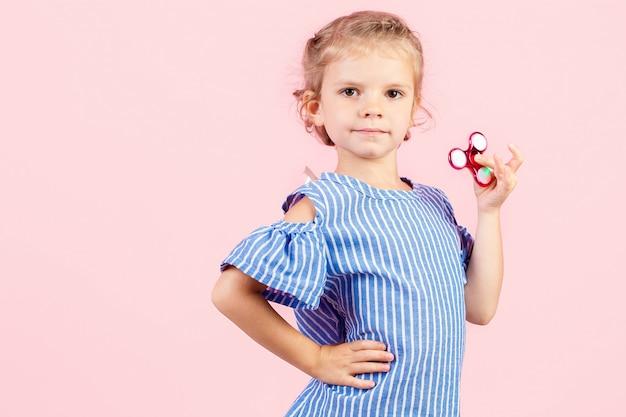 Fille en chemise rayée bleue joue spinner rouge dans la main