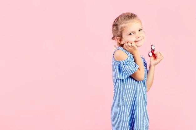 Fille en chemise rayée bleue joue spinner rouge à la main