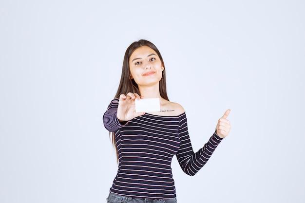 Fille en chemise rayée est titulaire d'une carte de visite et montrant le pouce vers le haut.