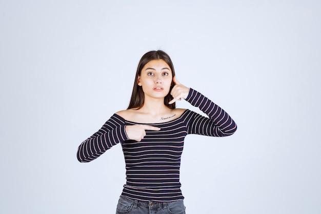 Fille en chemise rayée montrant le côté droit et demandant un appel.