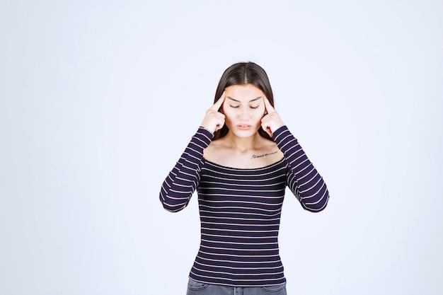Fille en chemise rayée pensant et analysant.