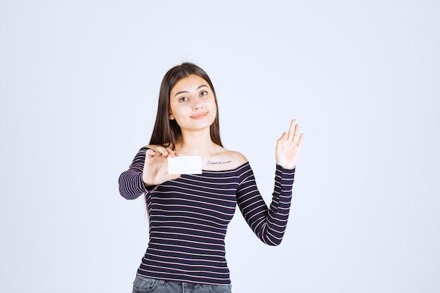 Fille en chemise rayée présentant sa carte de visite avec confiance.