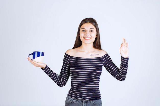 Fille en chemise rayée tenant une tasse de café et montrant un signe de plaisir.