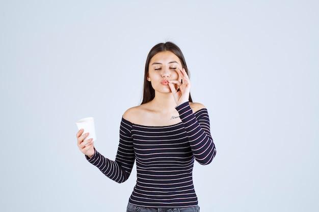 Fille en chemise rayée tenant une tasse à café en plastique et indiquant un bon goût.