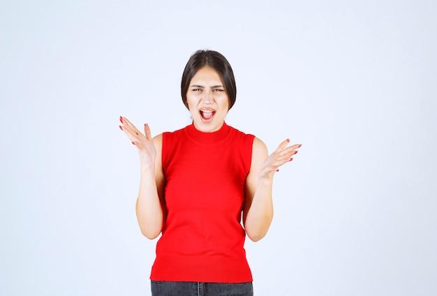 La fille en chemise rouge a l'air stressée et nerveuse.
