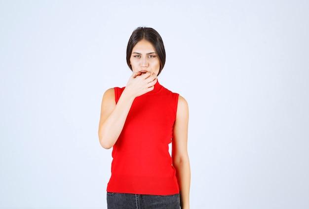 La fille en chemise rouge a l'air triste et déçue.