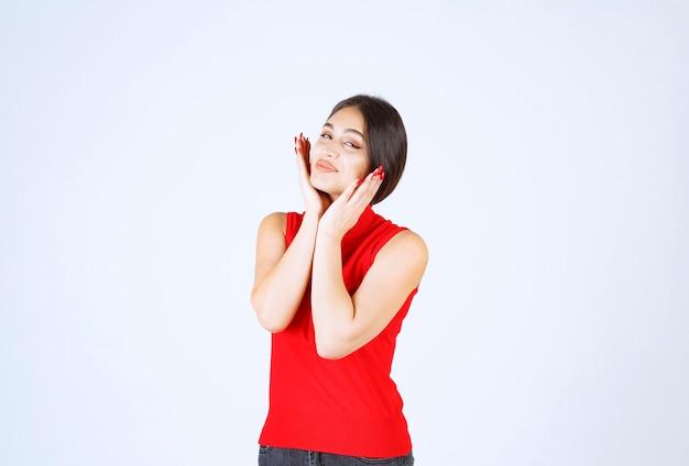 Fille en chemise rouge donnant des poses charmantes et séduisantes.