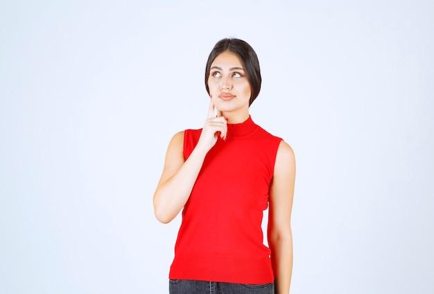 Fille en chemise rouge donnant des poses positives et séduisantes.