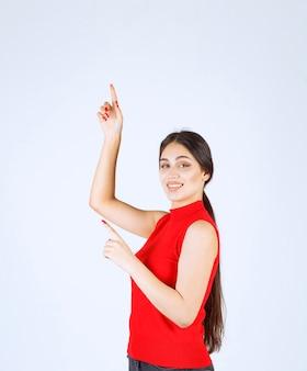 Fille en chemise rouge levant la main et pointant au-dessus.
