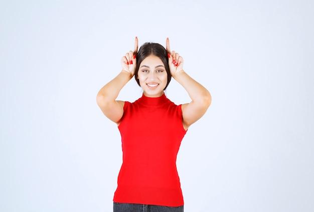 Fille en chemise rouge montrant des oreilles de loup.