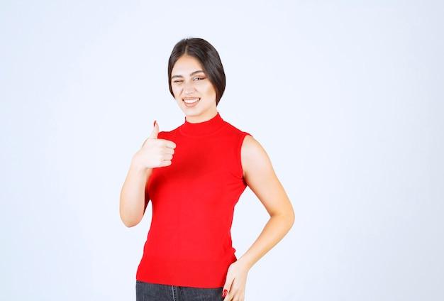 Fille en chemise rouge montrant les pouces vers le haut.