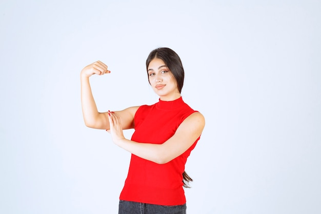Fille en chemise rouge montrant ses muscles du bras et ses poings.