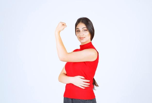 Fille en chemise rouge montrant ses poings et son pouvoir.