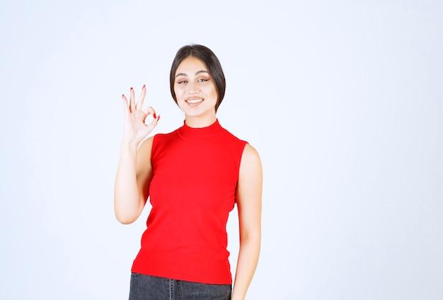 Fille en chemise rouge montrant le signe de la main de plaisir.