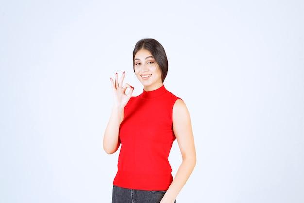 Fille en chemise rouge montrant un signe positif de la main.