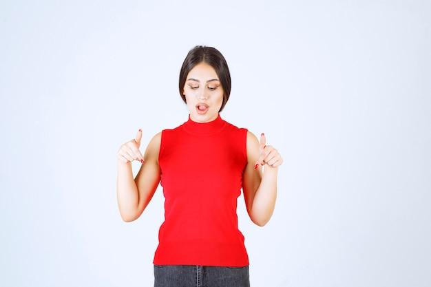 Fille en chemise rouge pointant quelque part en dessous.