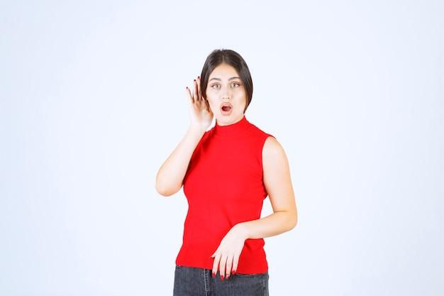Fille en chemise rouge pointant son oreille pour bien entendre.