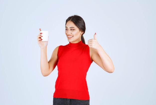 Fille en chemise rouge prenant un café et montrant un signe positif.