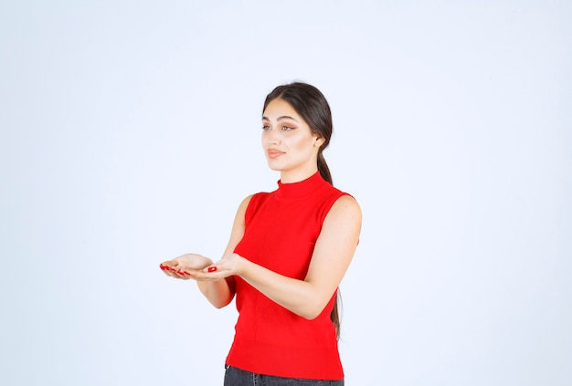 Fille en chemise rouge présentant et montrant quelque chose dans sa main.