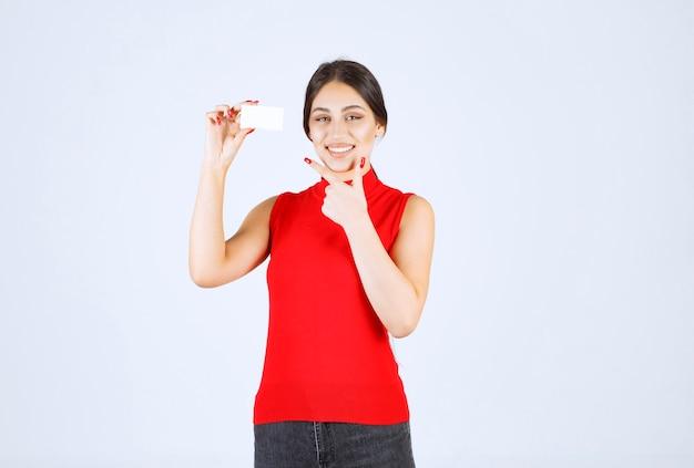 Fille en chemise rouge présentant sa carte de visite.
