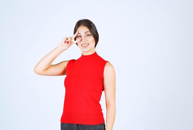 Fille en chemise rouge regardant à travers ses doigts.