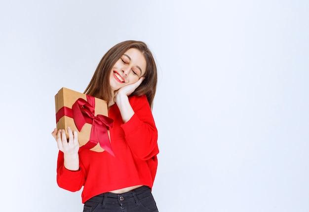 Fille en chemise rouge tenant une boîte-cadeau en carton enveloppée d'un ruban rouge.