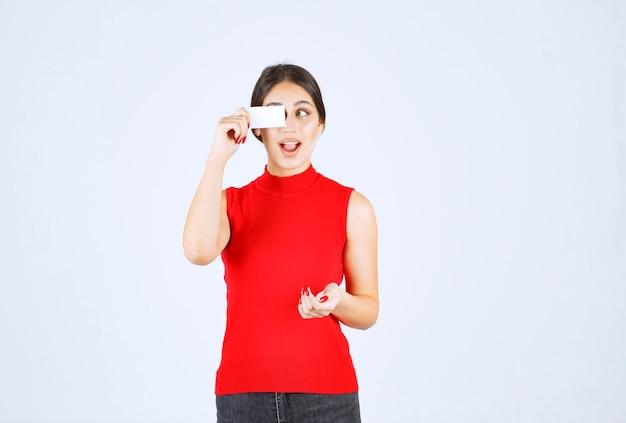 Fille en chemise rouge tenant une carte de visite et semble surprise.