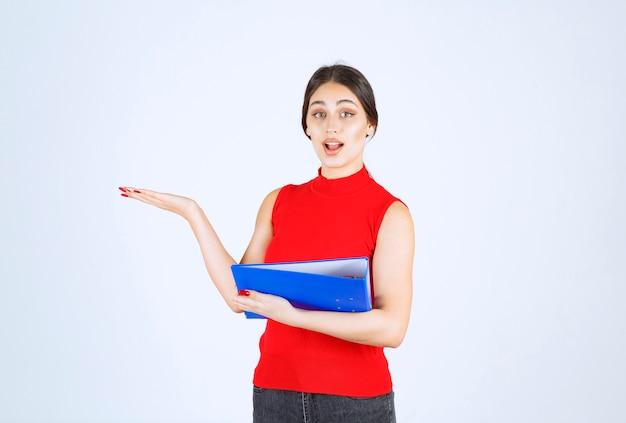 Fille en chemise rouge tenant un dossier d'affaires bleu.